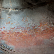African wildlife and human figures depicted in San bushman rock paintings, estimated at around 2000 years old, in Nswatugi Cave in Matobo National Park, Zimbabwe.
