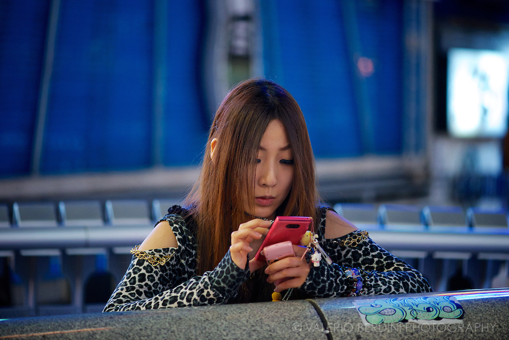 A girl checks her smartphone on ebisu-bashi bridge. Osaka, Japan 2013