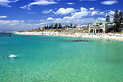 A perfect Cottesloe Beach summer day white sand, blue sky large white clouds and bright crystal clear green water.