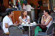 Three generations of women sit enjoying a drink on a Sunday afternoon, listening to jazz at a café opposite the Guggenheim museum in Bilbao.