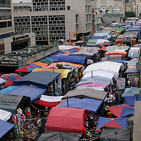 """Buhoneros - Hundreds of buhoneros' stalls line the boulevard in the Sabana Grande neighborhood of Caracas Monday, December 18, 2006.  Thousands of workers who sell products from clothing and accessories to household goods and bootleg DVDs make up the controversial """"informal economy.""""  While many Caracas residents complain that the buhoneros have taken over streets with their makeshift marketplace, many buhoneros give thanks to Venezuelan President Hugo Chavez for allowing them a way to survive by creating their own small businesses."""