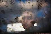 """A child is seen through the window of a train transporting refugees who have fled Syria, Iraq and Afghanistan during a brief stop at the station in Gedgelija ,Macedonia on  November 24,2017.The train transported the refugees near to the border of Serbia .Macedonia  declared they will only allow """"war-zone refugees"""" from Afghanistan, Iraq and Syria to transit through their country on their way to central and northern Europe.(Photo by Heidi Levine/Sipa Press)."""