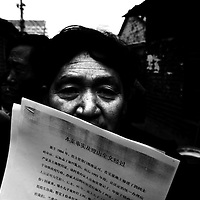 BEIJING, DECEMBER-22:  a man holds a law suit...Hundreds of thousands of Chinese have descended upon Beijing in the past decades hoping to get the attention of higher authorities for cival law cases reaching from work accidents, violence against family members, murder,  money extorsion and which in the majority reveal a corrupt rural legal system...The tradition of  appealing to higher authorities  in the capital reaches back to imperial times . In Beijing , petitioners villages where people would congregate in cheap housing, outside the city centre were common. These days though, petitioners increasingly face tremendous obstacles to get heard : provincial as well as undercover police try to stop petitioners from going to the National Petition offices to file law suites . If caught, they are briefly sent to an unoffical detention centre where they wait for the train ride back to the province.  In addition  the number of villages has been reduced significantly as the preparations for the 2008 Olympics progress. Many fear they will be all gone  by summer 2008. ..