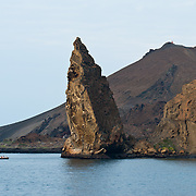A volcanic tuff cone rises above Pinnacle Rock on Bartolomé Island (Bartholomew Island), Galápagos Islands, Ecuador, South America. This large black partially eroded lava formation was created when volcanic magma reached the sea and exploded into particles which fastened together into rock comprised of thin layers. Bartolomé Island (or Bartholomew Island, named after Lieutenant David Bartholomew of the British Navy) is one of the geologically younger islands in the Galápagos archipelago, just off the east coast of Santiago (James) Island. The volcanic Galápagos Islands (officially Archipiélago de Colón, otherwise called Islas de Colón, Islas Galápagos, or Enchanted Islands) are distributed along the equator in the Pacific Ocean 972 km west of continental Ecuador, South America. In 1959, Ecuador declared 97% of the land area of the Galápagos Islands to be Galápagos National Park, which UNESCO registered as a World Heritage Site in 1978. Ecuador created the Galápagos Marine Reserve in 1998, which UNESCO appended in 2001.