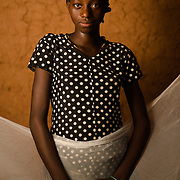 Mariam Ouedraogo (15) with her mosquito net in the village of Bore in the Sanmatenga region of Burkina Faso on 24 February 2014. Mosquito nets greatly decrease the incidence of malaria by reducing the risk of being bitten by the nocturnal Anopheles mosquito, which carries the malaria parasite.