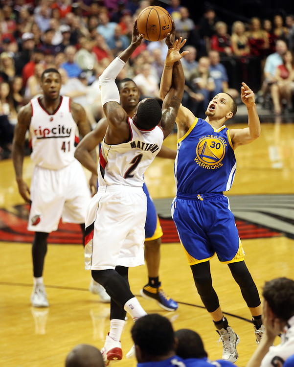 Wesley Matthews and Stephen Curry battle in the Moda Center arena as the Portland Trailblazers host the Golden State Warriors in an National Basketball Association game in Portland, Ore.