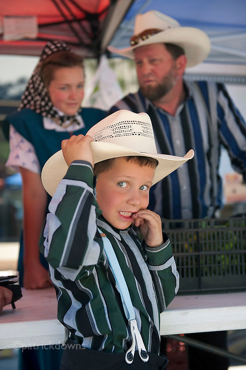 Portrait of a shy young Hutterite boy at the farmer's market. The numerous Hutterite colonies in MT supply much produce for the various markets.