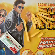 A place mat depicting bollywood movie stars, french fries and ketchup at the McDonalds fast food restaurant on the top floor of West End mall, Ludhiana, Punjab, India