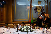 A child eats in a table while a guest kisses the groom at a Bolivian wedding in Bilbao.
