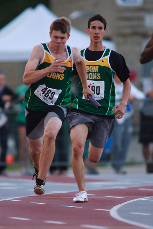 (London, Ontario}---09 June 2010) Alex Dawson of Earl of March (Kanata) receives the baton from teammate Jamie Johnston during the 4 X 100 meter relay heats at the 2010 OFSAA Ontario High School Track and Field Championships. Photograph copyright GEOFF ROBINS / Mundo Sport Images, 2010.