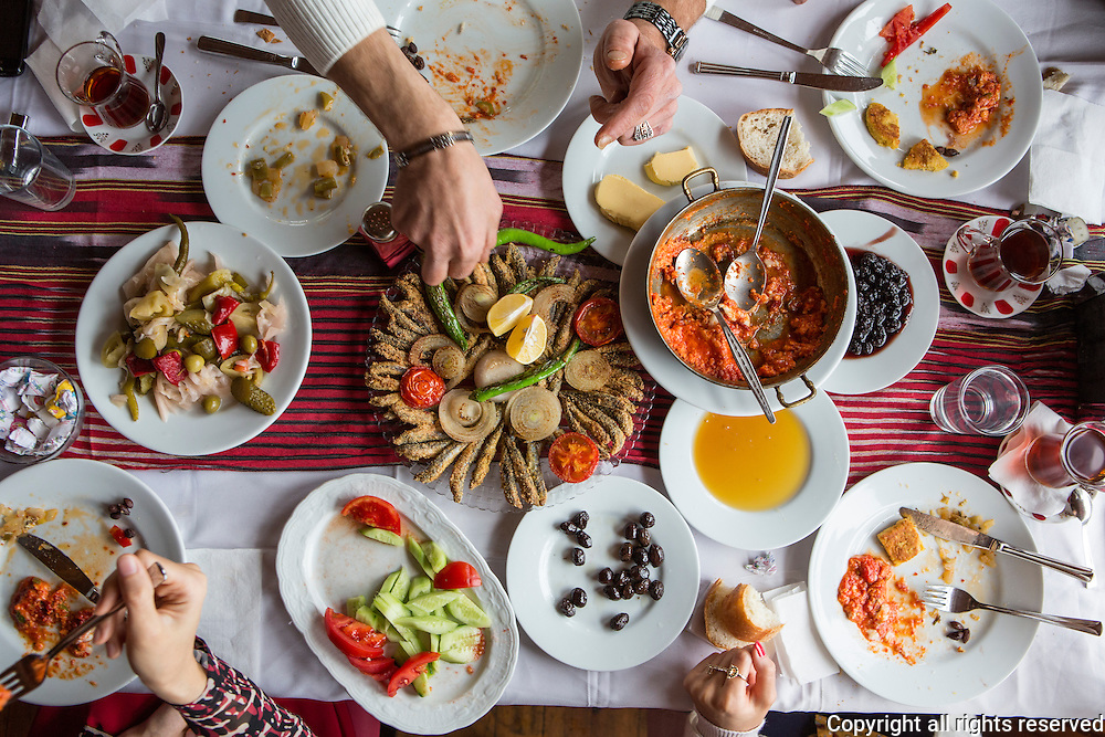 A feast of hamsi tava (anchovies dipped in cornmeal and fried in a skillet), menemen (fluffy scrambled eggs with tomatoes and peppers), pickles, olives, honey and fresh butter.
