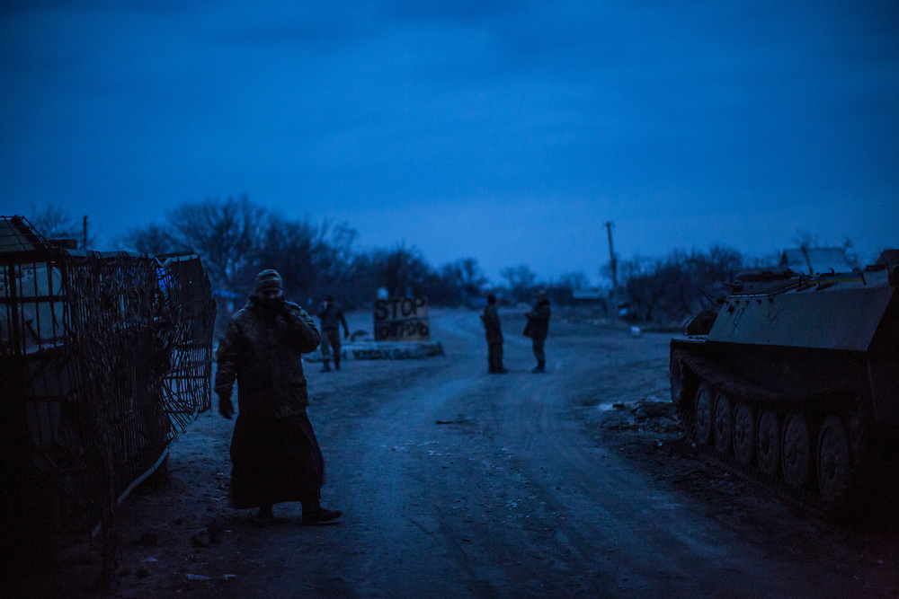 PERVOMAISKE, UKRAINE - MARCH 19, 2015: Father Vladimir, left, a volunteer chaplain, with members of the pro-Ukrainian Dnipro-1 battalion at one of the group's bases known as The Bridge near ongoing battles for the town of Pisky in Pervomaiske, Ukraine. CREDIT: Brendan Hoffman for The New York Times
