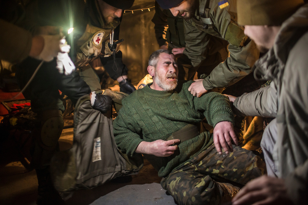 DEBALTSEVE, UKRAINE - FEBRUARY 8, 2015: An ambulance driver named Tariel, a Ukrainian Army medic, collapses in pain after receiving a shrapnel wound to the arm during shelling near a medical treatment point for Ukrainian fighters in Debaltseve, Ukraine. Fighting between pro-Russia rebels and Ukrainian forces there over the past two weeks has dealt steady casualties to Ukrainian fighters and civilians. CREDIT: Brendan Hoffman for The New York Times