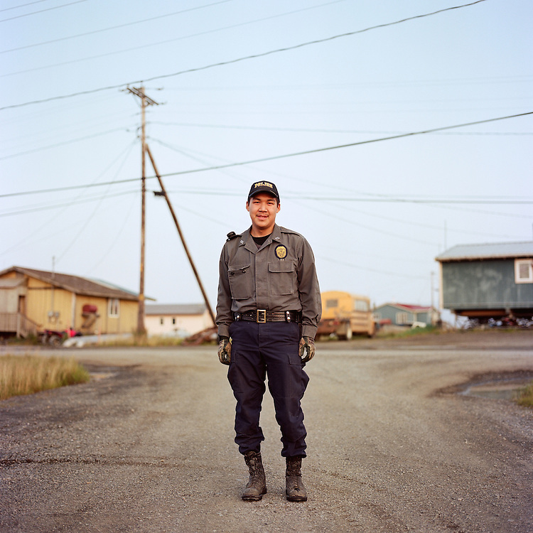"""I started this Monday. This is my first drunk call. I just want to help people, and make their lives better. I grew up here and in Bethel [Alaska].""—Phillip Charlie is the Village Police Officer in Quinhagak, Alaska. In many villages throughout rural Alaska, the first responders to public safety emergencies are Village Police Officers and Village Public Safety Officers whose work is supervised by Alaska State Troopers located in the larger regional hub towns like Bethel. Village Police Officers, unlike police officers in cities throughout the country, do not carry firearms. In 2014, there was a change in Alaska State law that will allow Village Public Safety Officers to receive training to carry firearms."