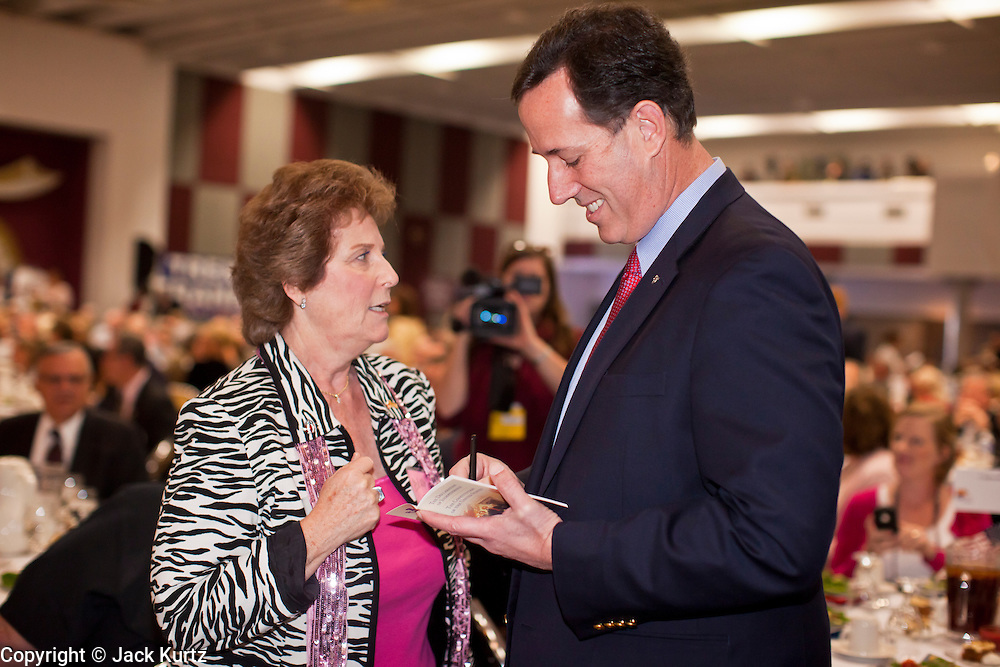 "21 FEBRUARY 2012 - PHOENIX, AZ:  Former US Senator and Republican Presidential candidate RICK SANTORUM signs a copy of the ""Declaration of Independence"" for a supporter at the Maricopa County Lincoln Day lunch in Phoenix. Santorum was in Phoenix Tuesday for an Arizona Republican party leadership luncheon ahead of the state's Republican Presidential Primary election and a CNN Republican Presidential Primary debate, which is Wednesday, Feb. 22.    PHOTO BY JACK KURTZ"