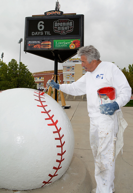 jt033117k/a sec/jim thompson/   Max Jaramillo of Jaramillo Painting touches up the red seams of the giant baseball infant of Isotopes Park Friday afternoon. The ball was first located at Tingley Fields from 1937-68 and was moved to the corner of University and Stadium in 1969 when the original Albuquerque Sports Stadium was built. Friday March 31, 2017. (Jim Thompson/Albuquerque Journal)