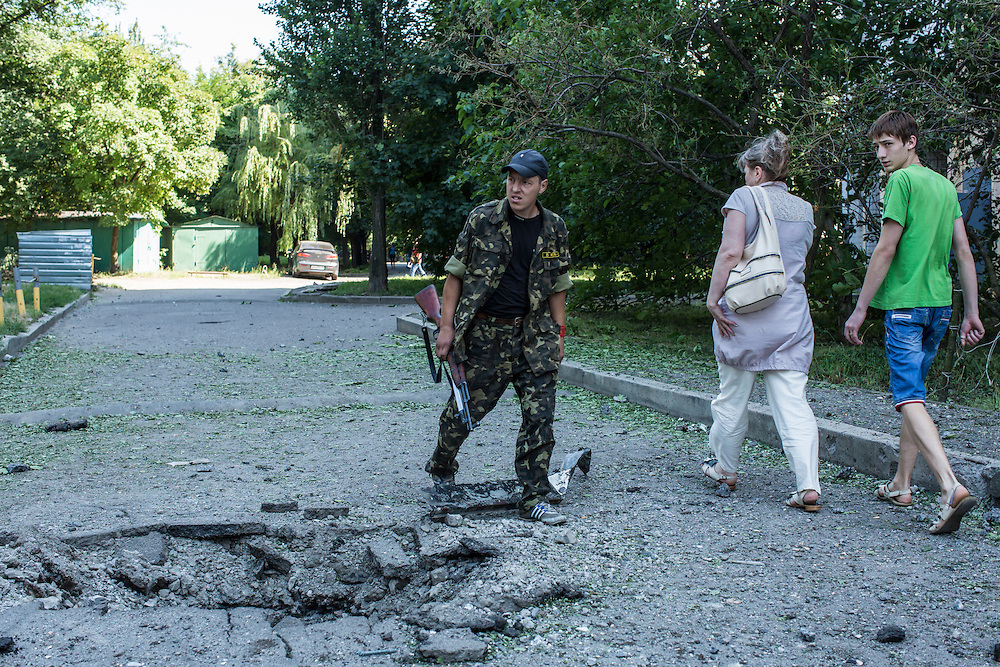 A pro-Russia rebel walks past a crater caused by a suspected grad rocket strike outside an apartment block on Tuesday, July 29, 2014 in Donetsk, Ukraine.