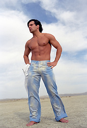shirtless man in bleached jeans outdoors on a dry lake bed