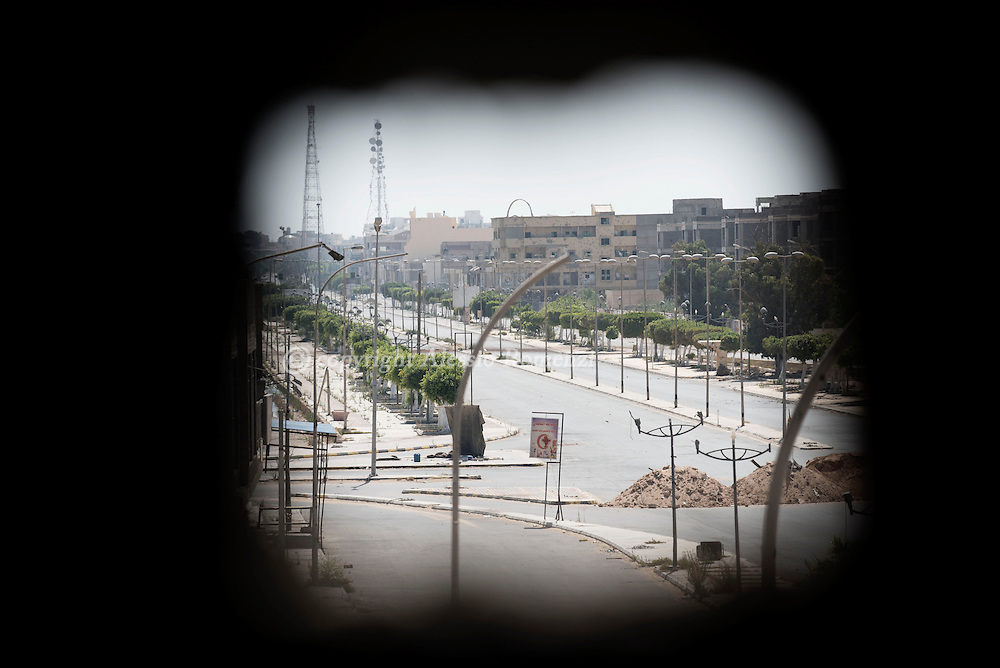 Libya: View through a hole in the wall of the part of the city in the hands of ISIS on the frontline with ISIS in Sirte. Alessio Romenzi
