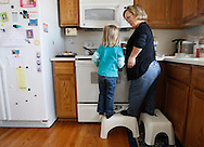 Barb Kotzian (R) talks with daughter Avery, 4 both standing on stools in their kitchen in Thornton, Colorado March 25, 2010.  Barb is a achondroplasia dwarf while Avery, 4 is average sized. Preferring to be called little persons Barb is active in the Little People of America, the only dwarfism support organization that includes all 200+ forms of dwarfism.  REUTERS/Rick Wilking (UNITED STATES)