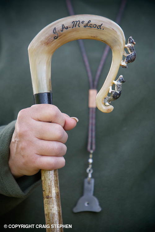 a shepherds crook and dog whistle at a sheepdog trial event.