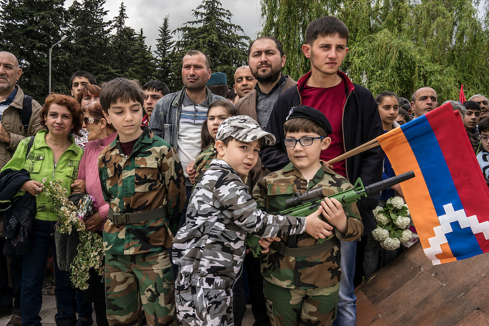 Audience members, including children in military costume, watch a ceremony commemorating both the victory over Nazi Germany in the Second World War as well as the fall of the strategic town of Shushi to Armenian forces on Monday, May 9, 2016 in Stepanakert, Nagorno-Karabakh.