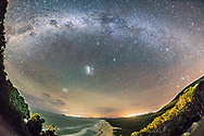 The southern Milky Way over the beach at Smoky Cape, NSW, Australia, looking into Hat Head National Park. I shot this from the back garden of the Smoky Cape Lighthouse, April 28, 2016, looking south toward the Magellanic Clouds and the main section of the southern Milky Way. The Southern Cross is at upper left; Orion is setting at far right. Sirius is at right and Canopus at centre. The lights on the horizon are from Kempsey. Sky colouration is from light pollution and from airglow.<br /> <br /> The sky is from a single 1-minute exposure at f/2.8 with the 15mm lens and Canon 6D at ISO 3200, untracked. The ground is from a mean combine stack of four 1-minute exposures to smooth noise in the foreground where it is more noticeable than in a starry sky. <br /> <br /> The beams from the lighthouse were sweeping across the scene as I took these exposures but the long exposures and fast motion of the beams blurred them out of visibility. They are lighting the hills. Foreground illumination is from house lights and a yard light.