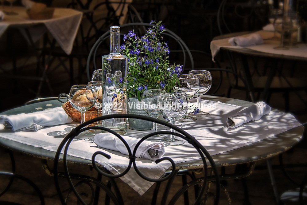 A cafe table in Avignon with wine glasses, water bottle, purple flowers and bread basket.