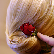 A rose is placed in the hair of a bridesmaid as final hair and makeup preparations are made.