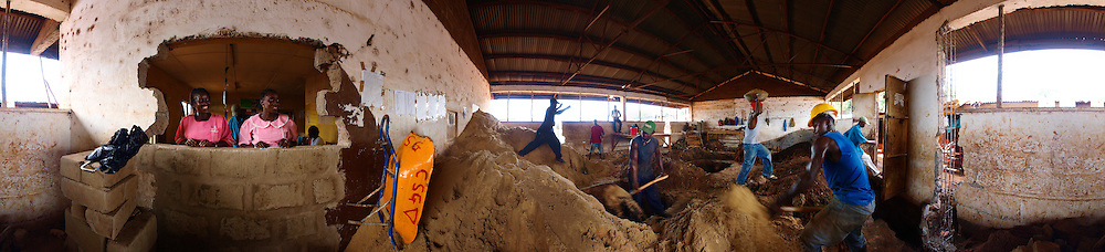 Nurses watch some of the work as it progresses, during the renovation of Kroo Bay health center. Kroo Bay, Freetown, Sierra Leone.