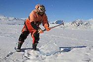 Marine chemist Melissa Chierici (Institute of Marine Research) uses ice pick to collect samples of glacial ice from lonely chunk sitting atop frozen fjord; Kongsfjord, Svalbard, Norway.
