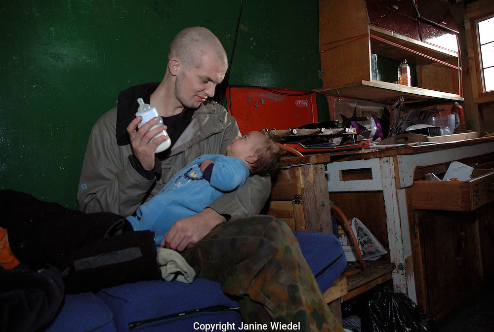 Young man bottle feeding baby in caravan St Agnes Place Squat South London