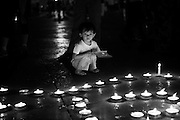 A young chinese girl joins in the rally by predominantly the youth contingent of Chegndu city in front of the Municipal Peoples Congress building in Chengdu. They were calling for unity amongst the peoples of the province and chanting words such as youjin (strong) and Jiaoxing Chengdu (Wake up Chengdu)..Candles were lit to form heart shaped symbols with the numbers 5-12, the date of last weeks earthquake which has to date officially killed 30,000 people..