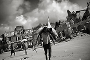 At the fish marked in the old center of mogadishu a man carries a shark on his shoulders to bring it to the  markedplace.