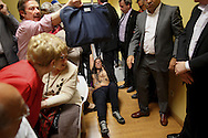 MADRID, SPAIN - MAY 05: Men drag a Femen activist and a woman kicks her leg after the activist tried to climb on stage during a speech of President of Popular Party in Madrid Esperanza Aguirre (not in picture) at the Cultural Center of Arganzuela on May 5, 2014 in Madrid, Spain. Femen activists protested during a Madrid Popular Party Euro Election rally with body painting reading 'Fascist ePPidemic'. (Photo by Pablo Blazquez Dominguez/Getty Images)
