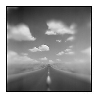 USA, Arizona, Springerville, Blurred black and white image of cumulus clouds above US Highway 60 road through desert
