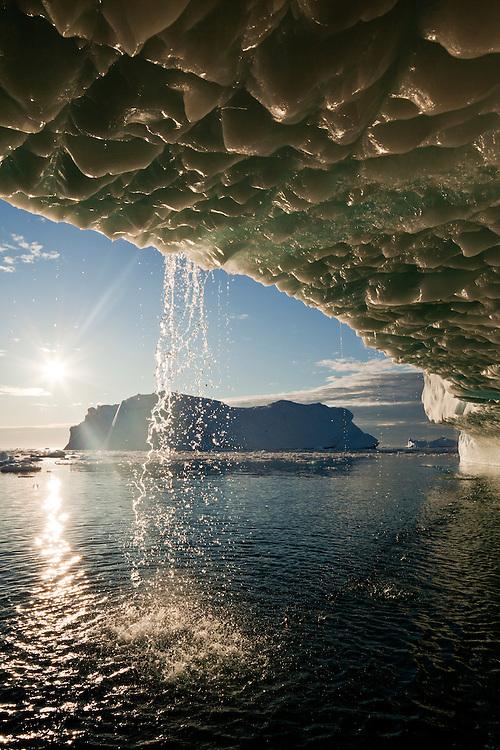 Greenland, Ilulissat, Midnight sun lights melting icebergs calved from Jakobshavn Glacier floating in Disko Bay on sunny summer afternoon