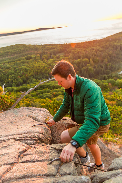 """A man hiking """"The Beehive"""" in fall in Maine's Acadia National Park."""