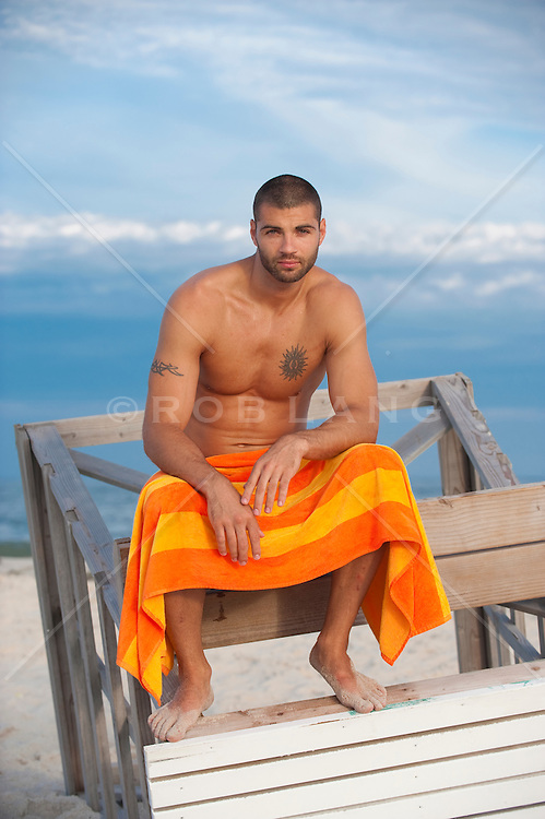 Good looking man in a towel seated on a lifeguard stand at the beach