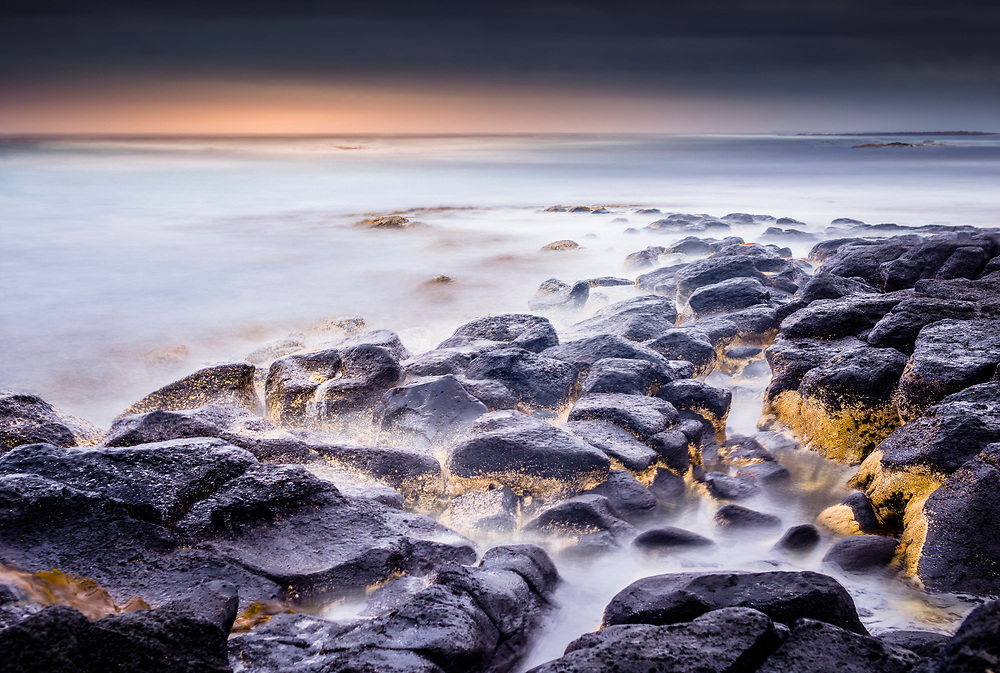 Sunset over rocks on at Port Fairy, Victoria. Waves lapping the rocks have been rendered to a mist by using a long exposure and stacking of multiple images.