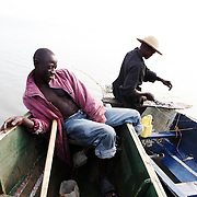Augustino Ssekisaka (left) and  Siggando Francis spend their morning fishing on Lake Victoria. Here in Ggaba, a small town in southern Uganda that almost entirely subsists on the fishing industry, the locals have contributed to the dangerous overfishing of the lake despite strict regulations from Tanzania, Uganda, and Kenya. Fishermen continue to keep fish that are far below the required minimum weight and employ dymanite and poison.
