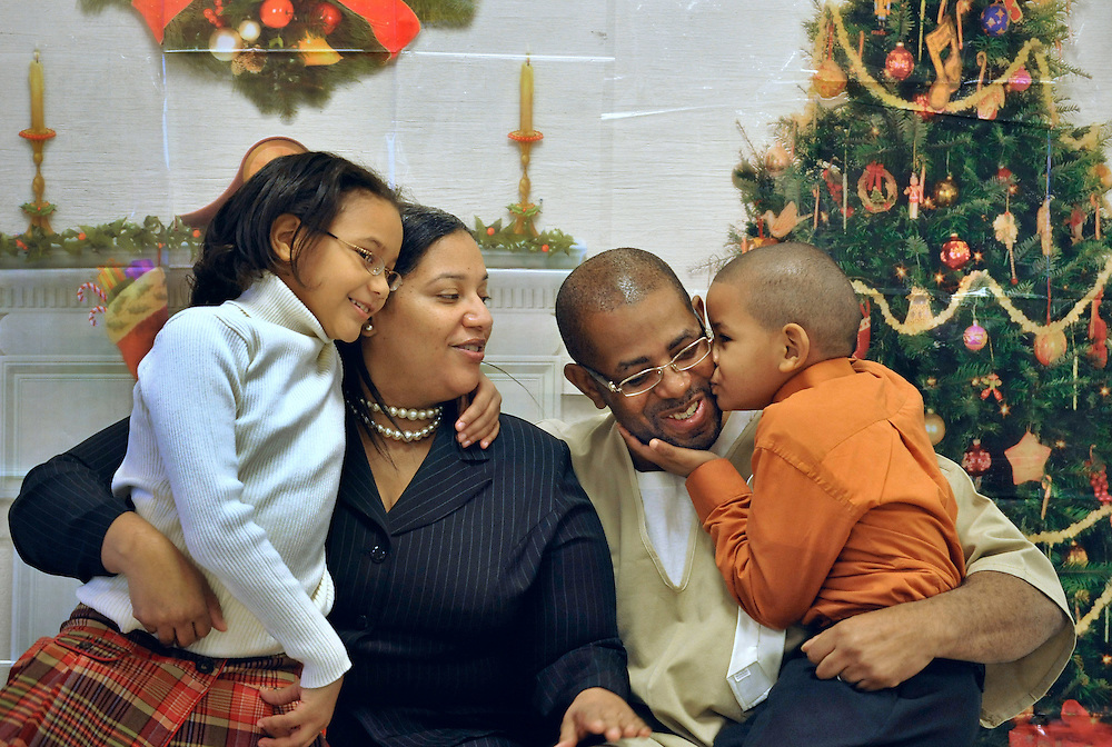 In this Tuesday, Dec. 14, 2010 photo, Christopher Garvin, Jr., 5, right, kisses his father, Christopher Garvin, Sr., as sister Crystal, 7, left, and their mother Sheila Harris look during a holiday party for graduates of the Inside Out at Carl Robinson Correctional Institution in Enfield, Conn.  (AP Photo/Jessica Hill)