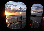 A ferry passenger watches the sunset while riding on the ferry from Southworth to Fauntleroy during a stormy September evening. <br /> <br /> Erika Schultz / The Seattle Times