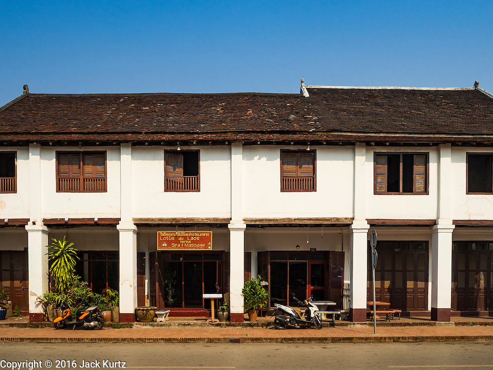 "13 MARCH 2016 - LUANG PRABANG, LAOS: A colonial era house that has been refurbished and turned into a spa in Luang Prabang. Luang Prabang was named a UNESCO World Heritage Site in 1995. The move saved the city's colonial architecture but the explosion of mass tourism has taken a toll on the city's soul. According to one recent study, a small plot of land that sold for $8,000 three years ago now goes for $120,000. Many longtime residents are selling their homes and moving to small developments around the city. The old homes are then converted to guesthouses, restaurants and spas. The city is famous for the morning ""tak bat,"" or monks' morning alms rounds. Every morning hundreds of Buddhist monks come out before dawn and walk in a silent procession through the city accepting alms from residents. Now, most of the people presenting alms to the monks are tourists, since so many Lao people have moved outside of the city center. About 50,000 people are thought to live in the Luang Prabang area, the city received more than 530,000 tourists in 2014.    PHOTO BY JACK KURTZ"