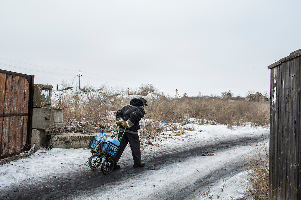 NYZHNIA KRYNKA, UKRAINE - JANUARY 27, 2015: Yevgeniy, 75, hauls drinking water from a well to his home in Nyzhnia Krynka, Ukraine. After intense fighting in the area over the summer, residents are still facing severe difficulties affording food. CREDIT: Brendan Hoffman for The New York Times