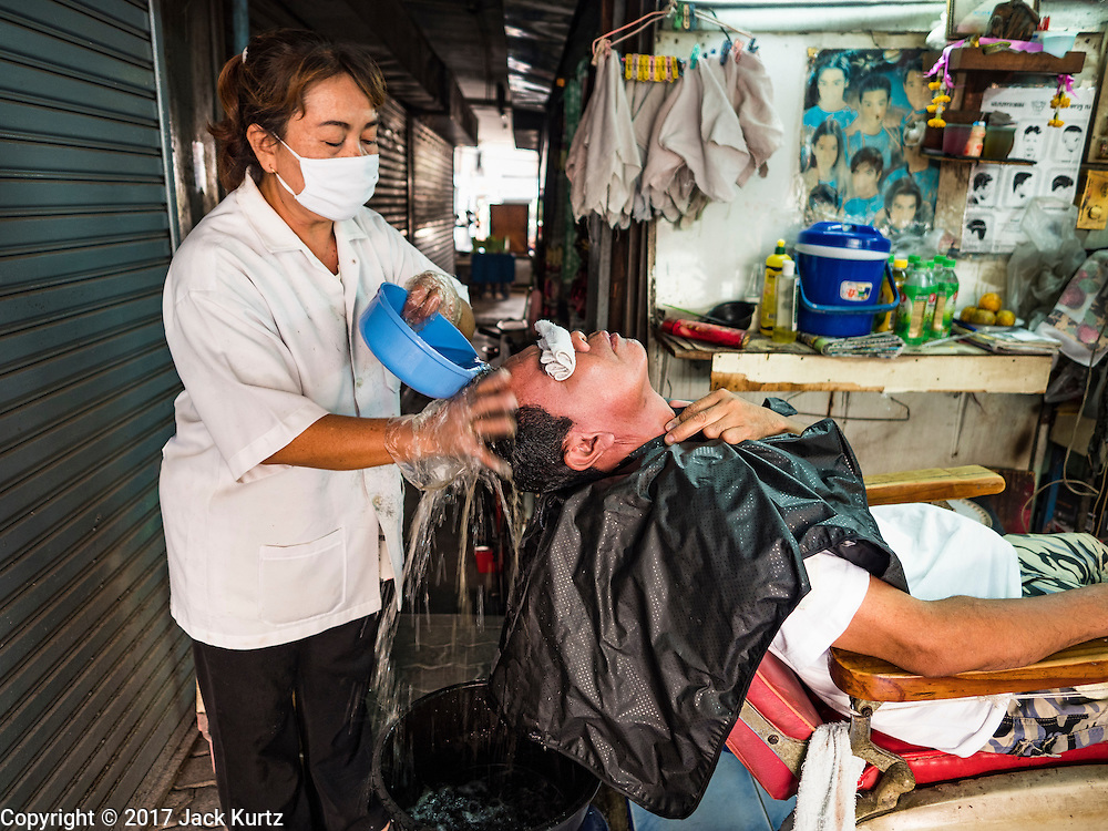 "06 FEBRUARY 2017 - BANGKOK, THAILAND: A barber washes a customer's hair in her small shop in what used to be known as Kalabok Market under the Phra Khanong Bridge in the Phra Khanong district of Bangkok. Kalabok is the Thai word for hairdresser and the market was called Kalabok because there were many barbershops and hairdressers under the bridge. In 1985, the city changed the name of the market to ""Singha Market."" There are still about 10 small men's barbershops, most with just one barber, and four women's salons, most with one hairdresser,  under the bridge.      PHOTO BY JACK KURTZ"