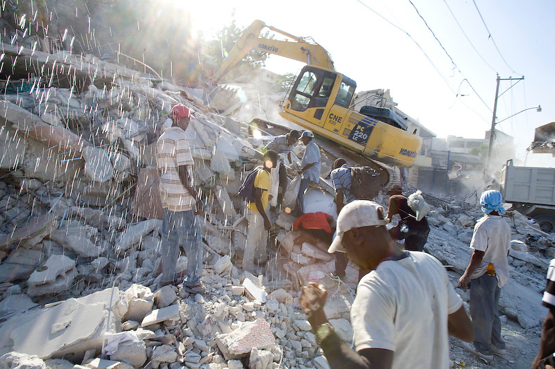A bulldozer pulls bodies out of rubble on Delmas road. Port Au Prince, Haiti. Photo by Ben Depp.1/20/2010.