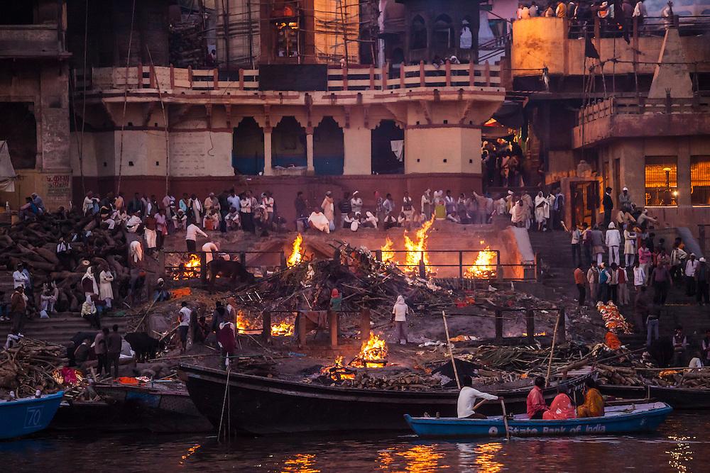 The open funeral pires / cremation fires at Manikarnika Ghat along the Ganges river, Varanasi, Uttar Pradesh, India.