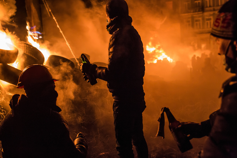 KIEV, UKRAINE - JANUARY 25: Anti-government protesters prepare to throw Molotov cocktails during clashes with police on Hrushevskoho Street near Dynamo stadium on January 25, 2014 in Kiev, Ukraine. After two months of primarily peaceful anti-government protests in the city center, new laws meant to end the protest movement have sparked violent clashes in recent days. (Photo by Brendan Hoffman/Getty Images)