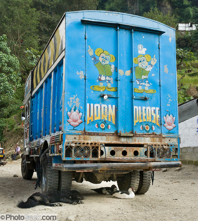 """A dog sleeps and ducks rest beneath a truck, with """"Horn Please"""" sign, in the town of Naya Pul, an important gateway to the Annapurna Conservation Area, in Nepal."""